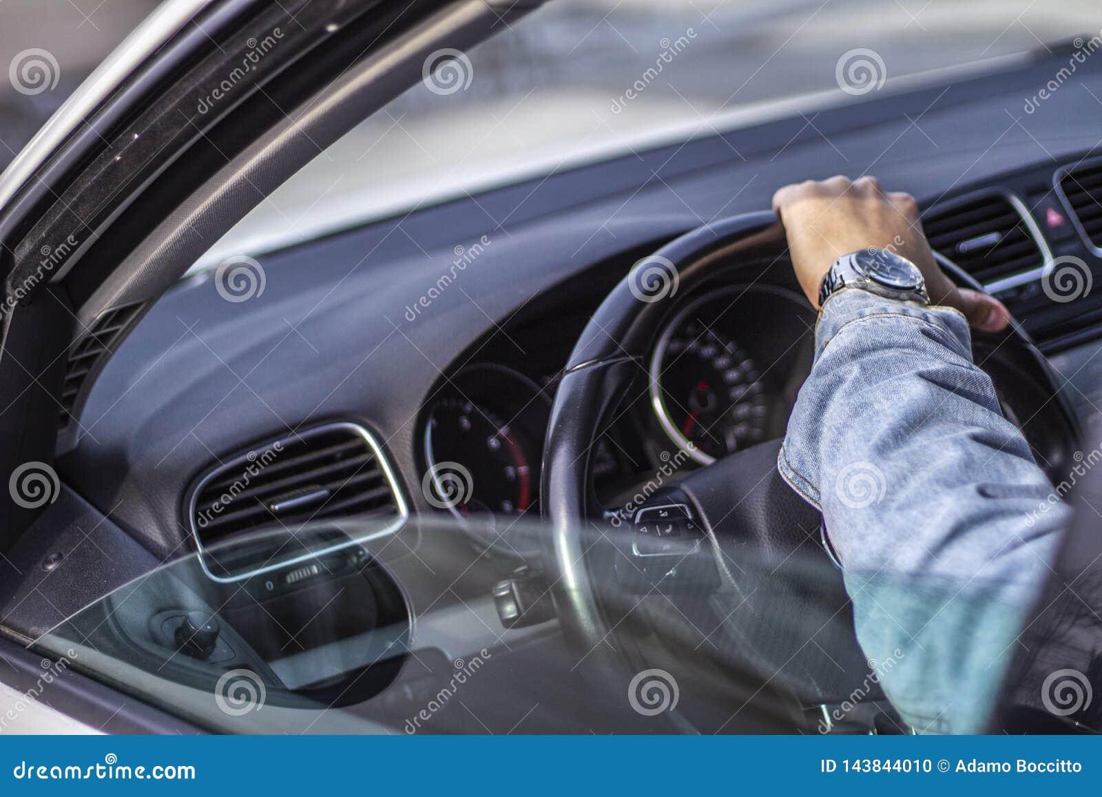 Sopra - il colpo della spalla di un giovane che tiene il volante dell automobile
