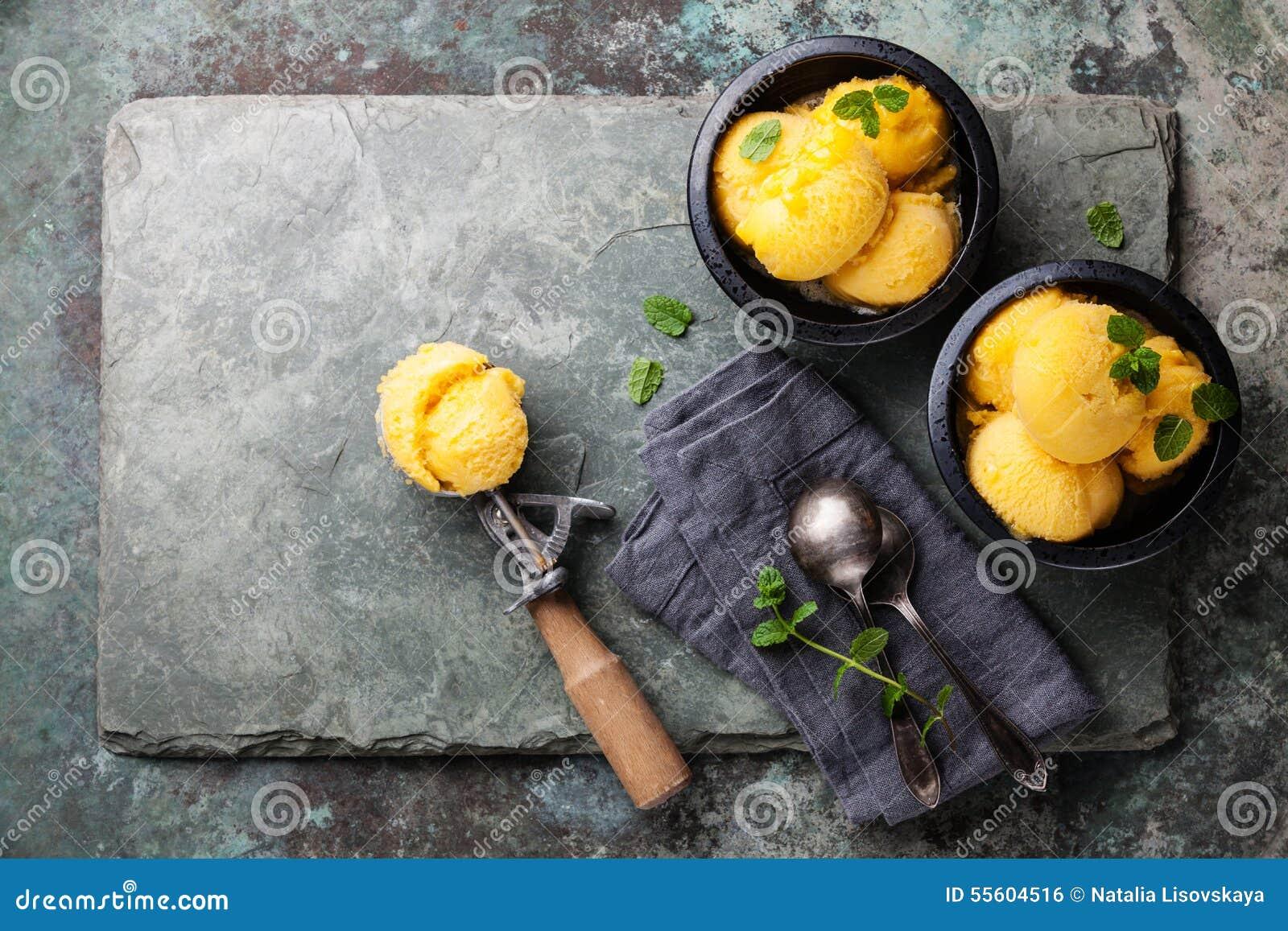 Sorbetto del gelato del mango con le foglie ed il cucchiaio di menta per il gelato