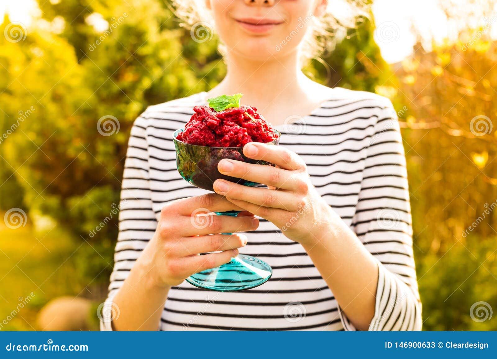 Sorbetto in mani della ragazza - dessert di rinfresco del lampone di estate