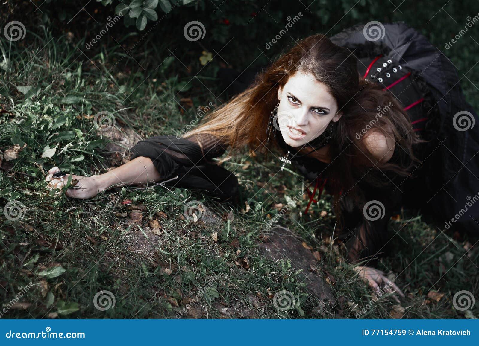 Sorcière de Halloween dans une belle jeune femme de forêt foncée dans le costume de sorcières Conception d art de Halloween Fond