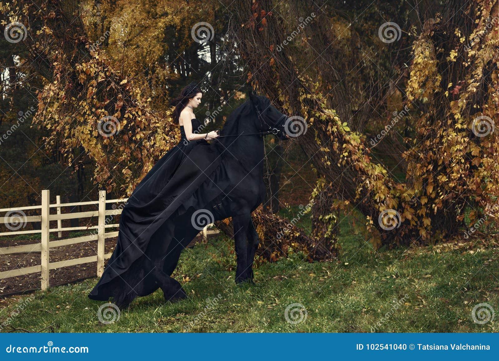 Sorcière noire de reine à cheval sur un cheval noir dans une forêt sombre