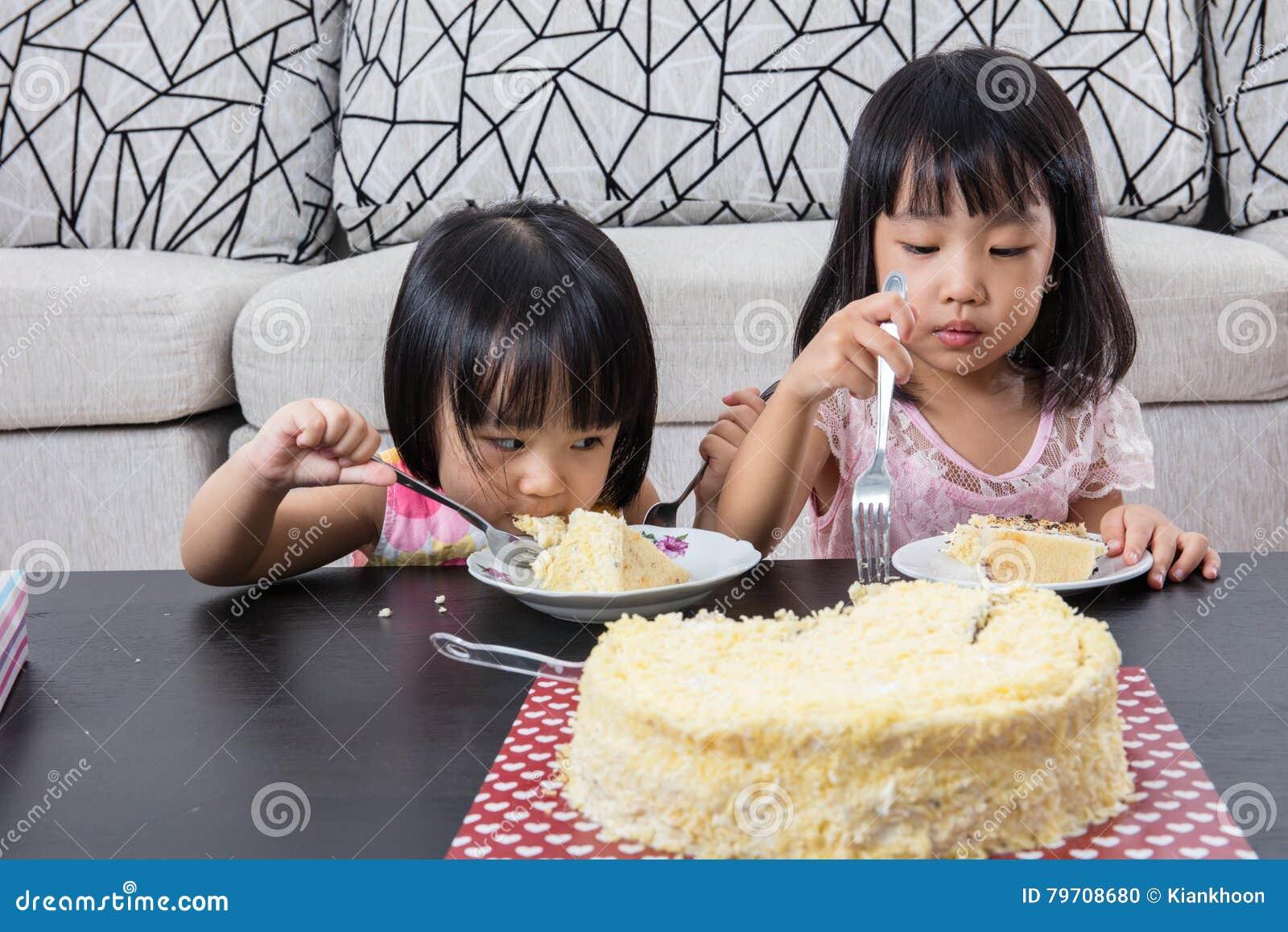 Sorellina cinese asiatica che mangia la torta di formaggio di compleanno