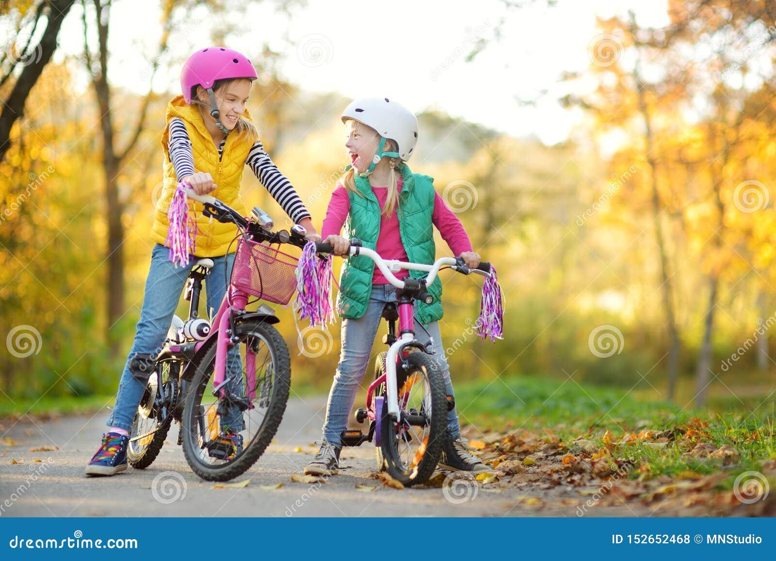 Sorelline sveglie che guidano le bici in un parco della citt? il giorno soleggiato di autunno Svago attivo della famiglia con i b