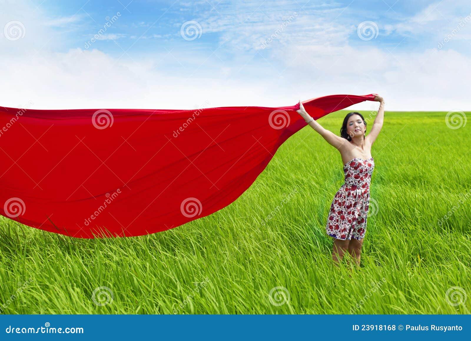 Sorglose Frau mit rotem Schal auf Reisfeld