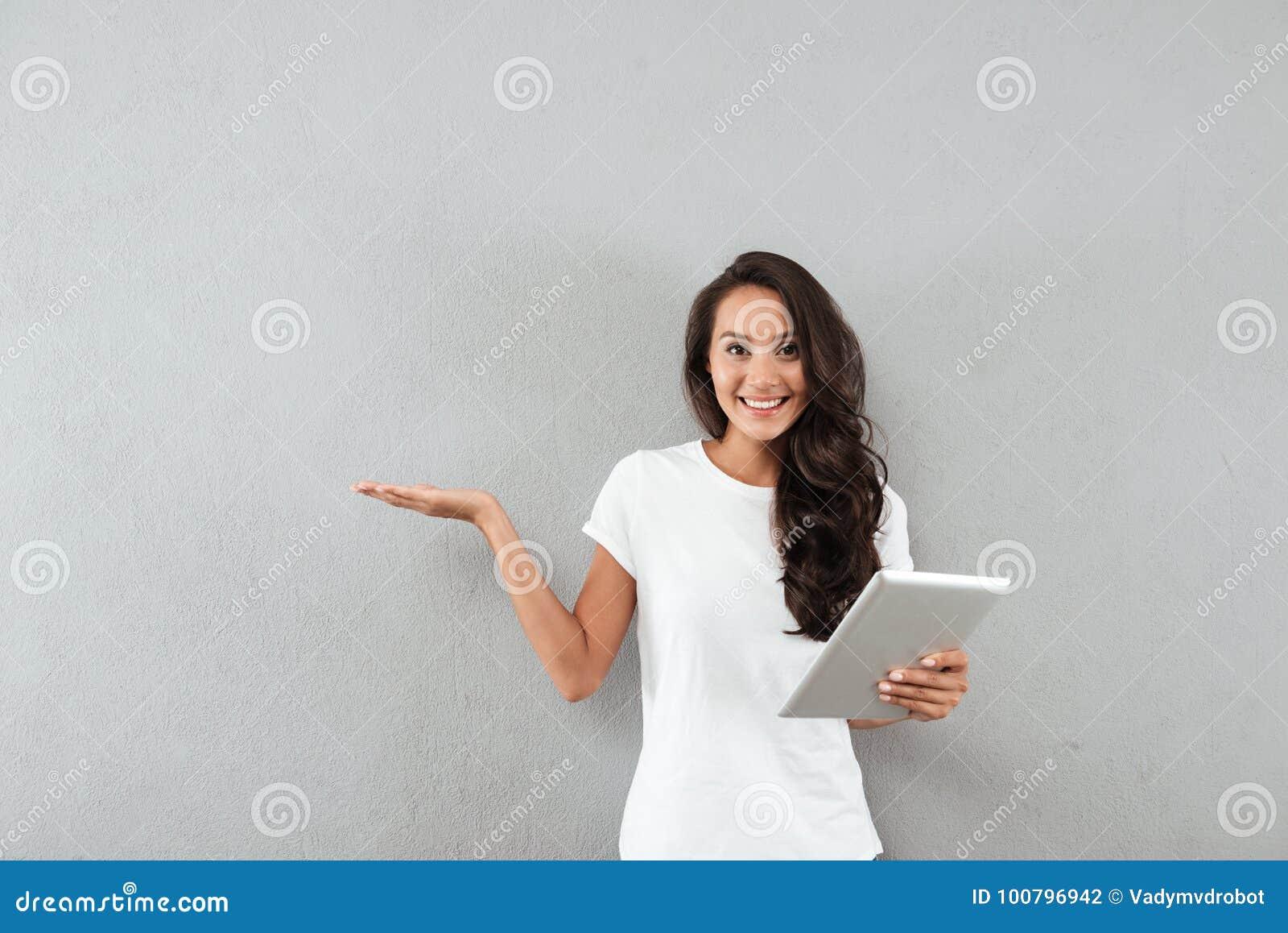 Sorridere computer abbastanza asiatico della compressa della tenuta della donna