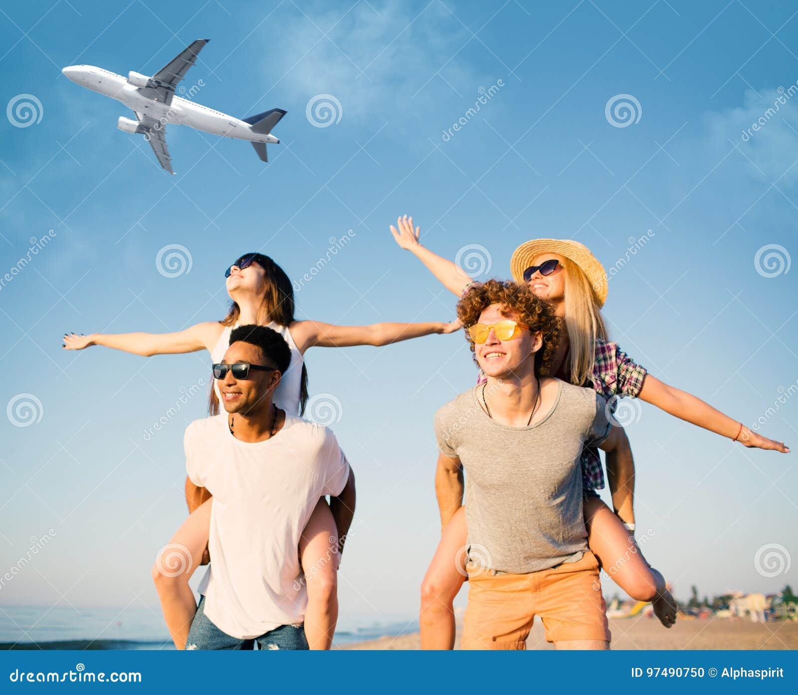 Sorridere felice accoppia il gioco alla spiaggia con gli aerei nel cielo