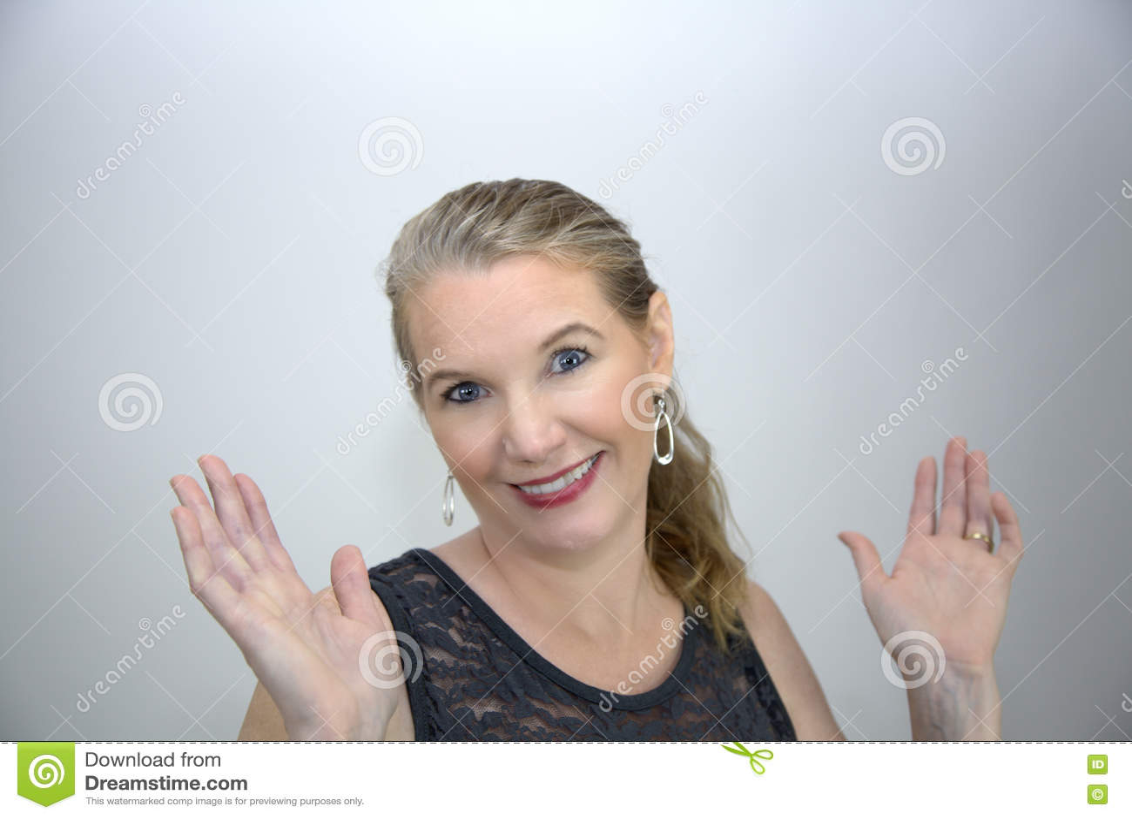 Sorridere femminile biondo maturo con entrambe le mani su
