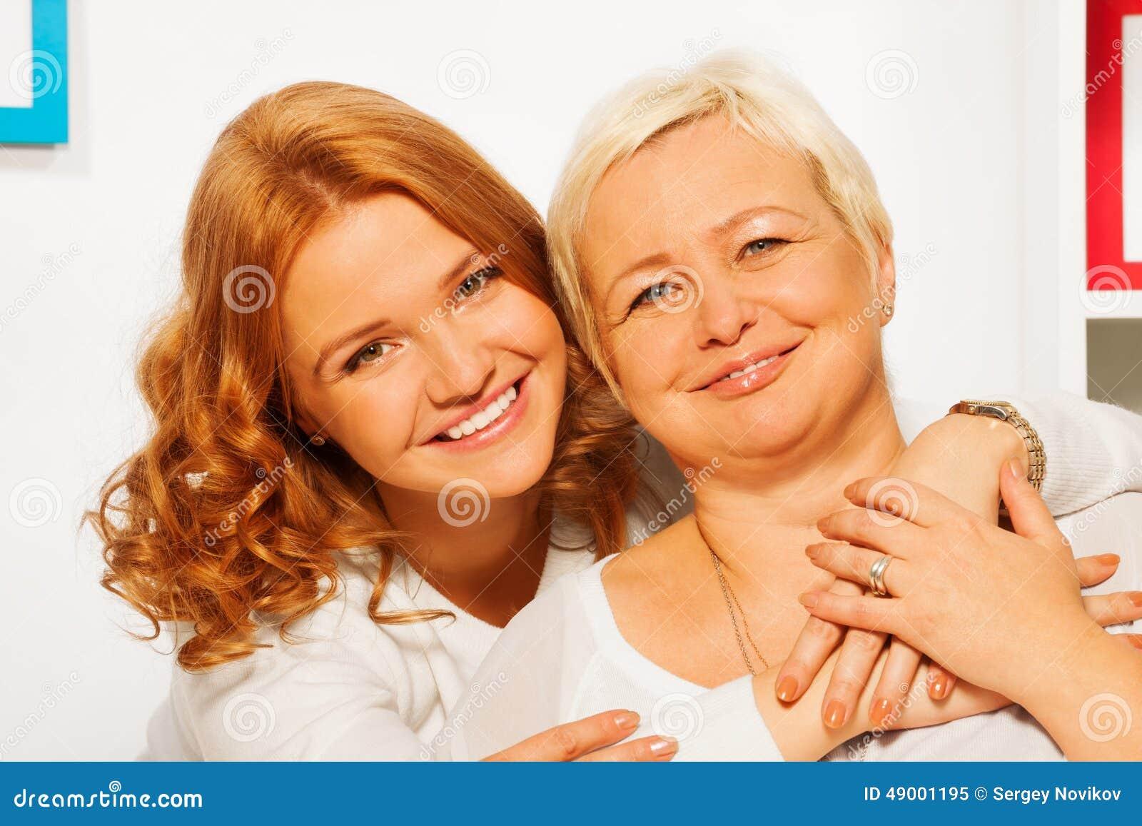 Sorrindo e abraçando a filha com mãe idosa