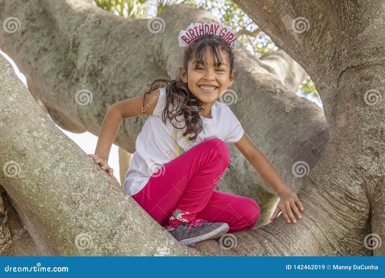 Sorrisi di una ragazza di buon compleanno dalla cima dell albero