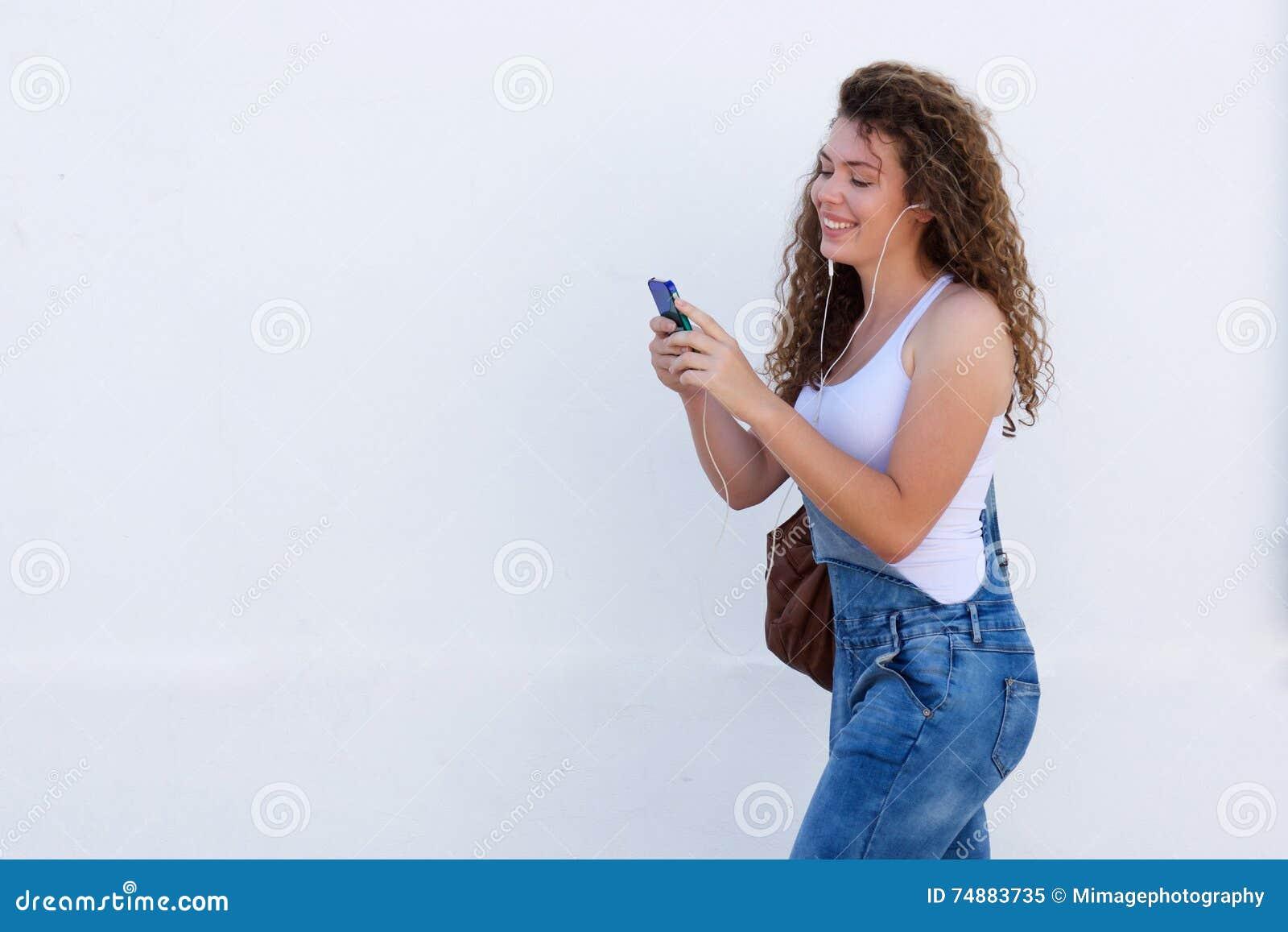 Sorriso adolescente com passeio do telefone celular e dos fones de ouvido