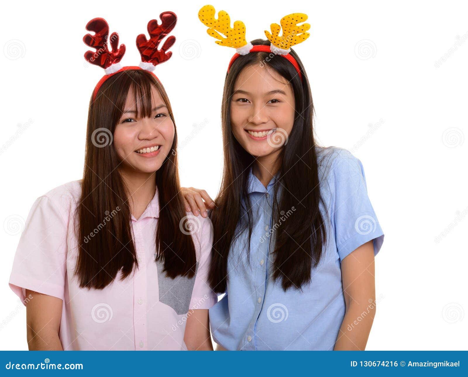 Sorriso asiático feliz novo de dois adolescentes pronto para o Natal