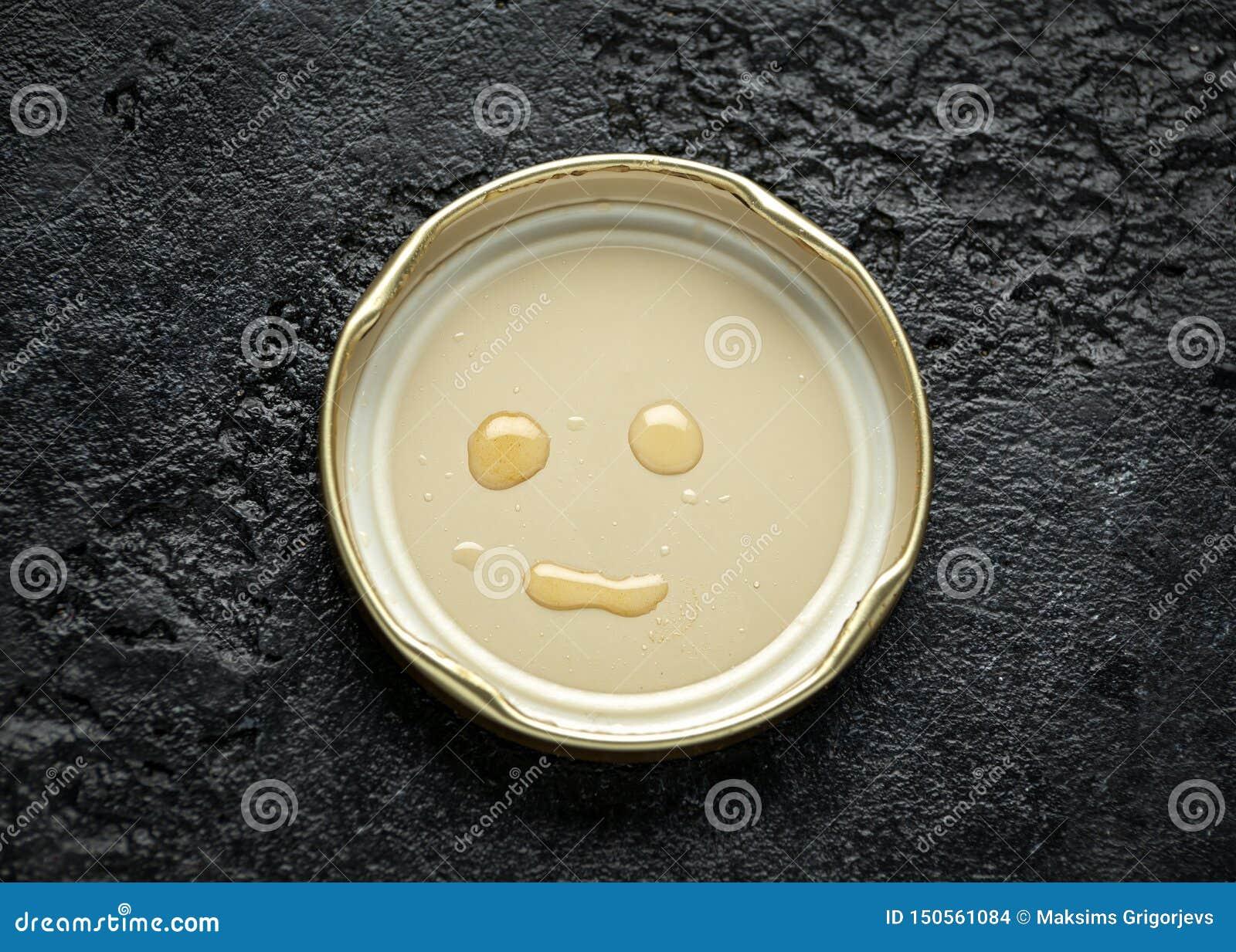 Sorriso da cara feito com gotas do mel na tampa