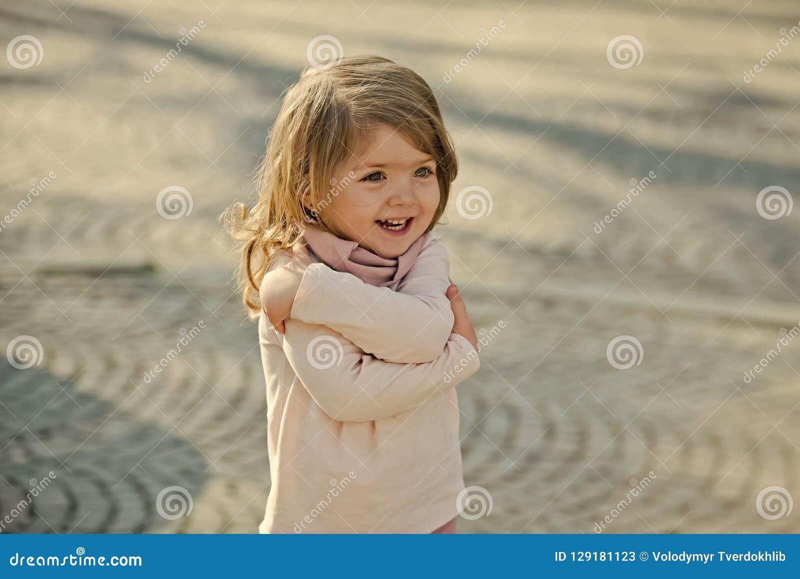 Sorriso da criança com gesto de mão do abraço no dia ensolarado
