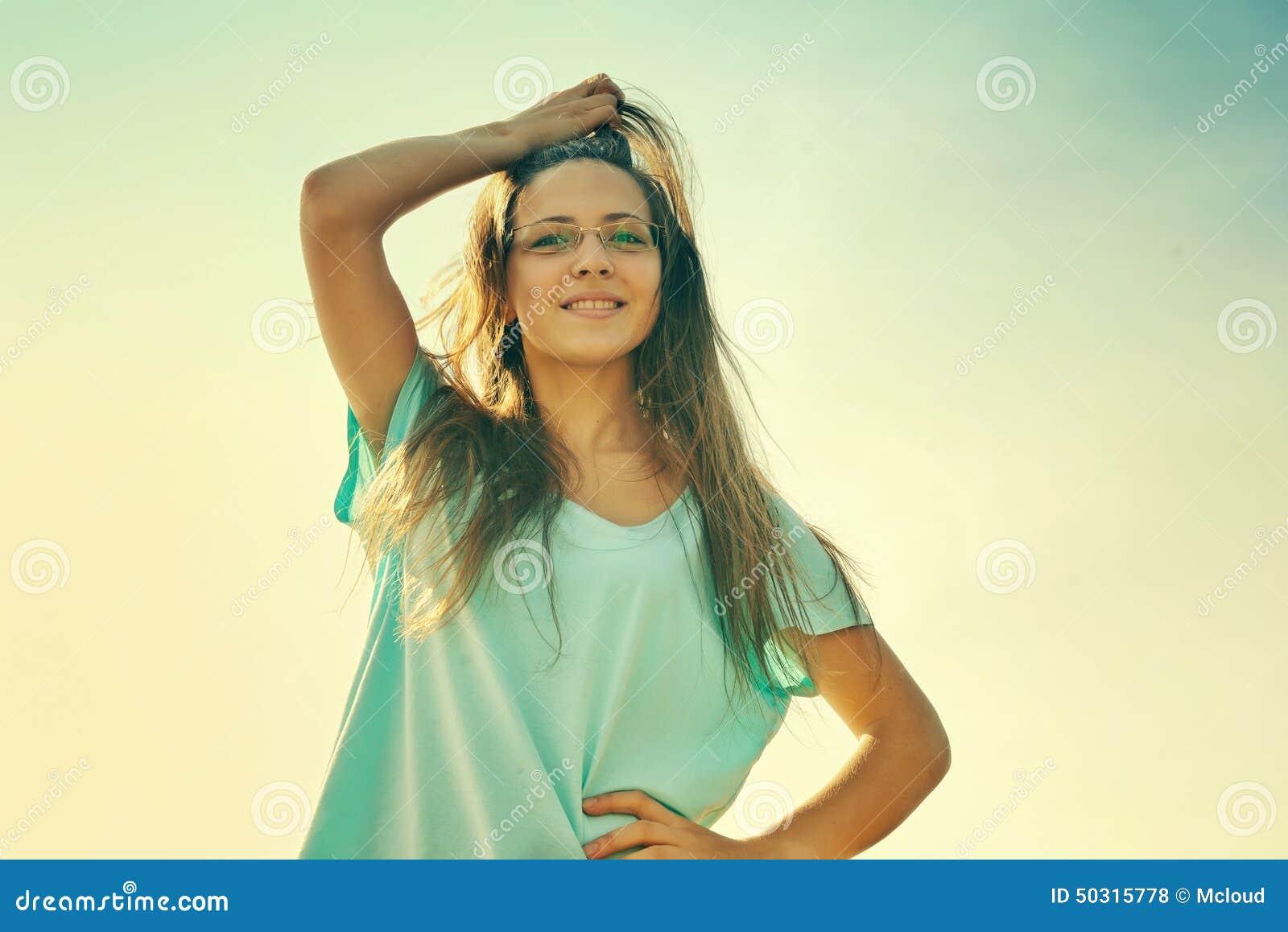 Sorriso da menina alegre, amigável e encantamento olhando a câmera no dia de verão ensolarado morno