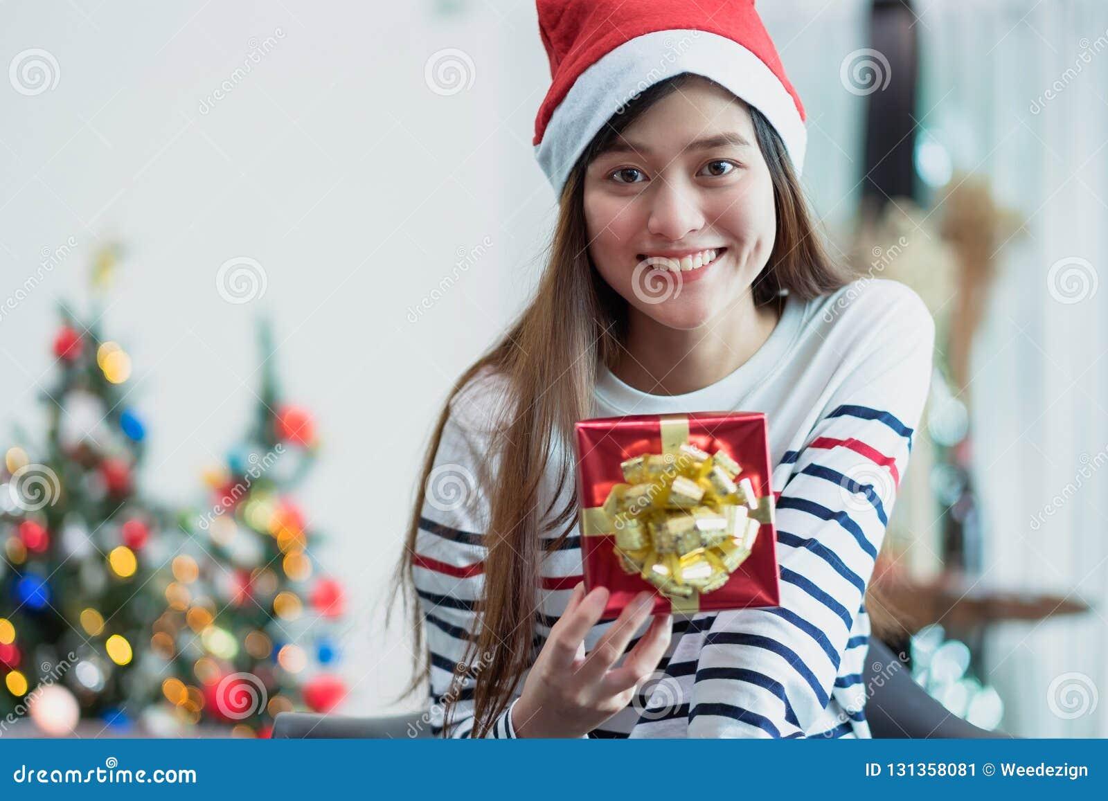 Sorriso da mulher de Ásia que guarda a caixa de presente do xmas do ouro na sagacidade da festa natalícia