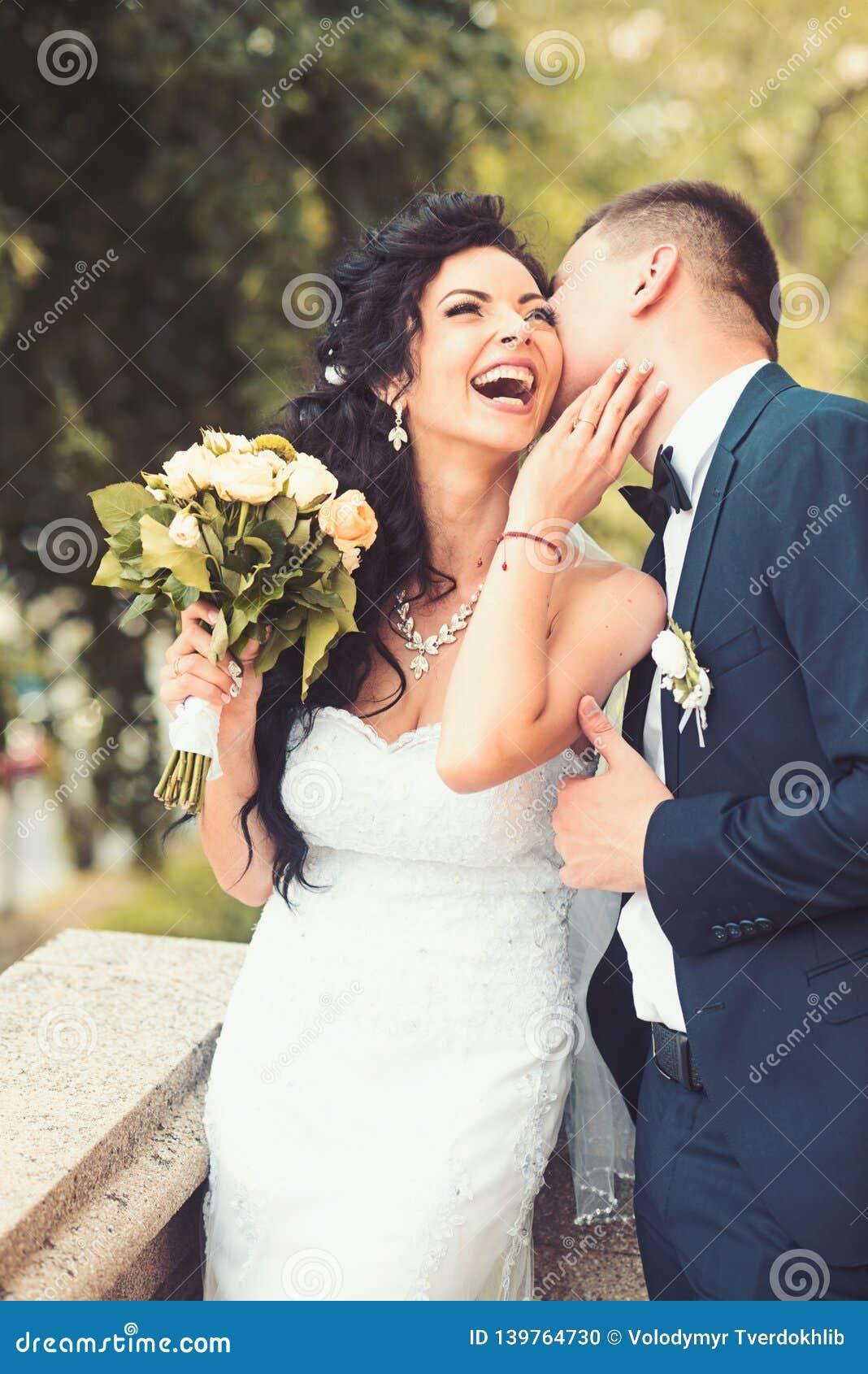 Sorriso da mulher e do homem no dia do casamento Noiva feliz do beijo do noivo com ramalhete Pares do casamento no amor Pares do