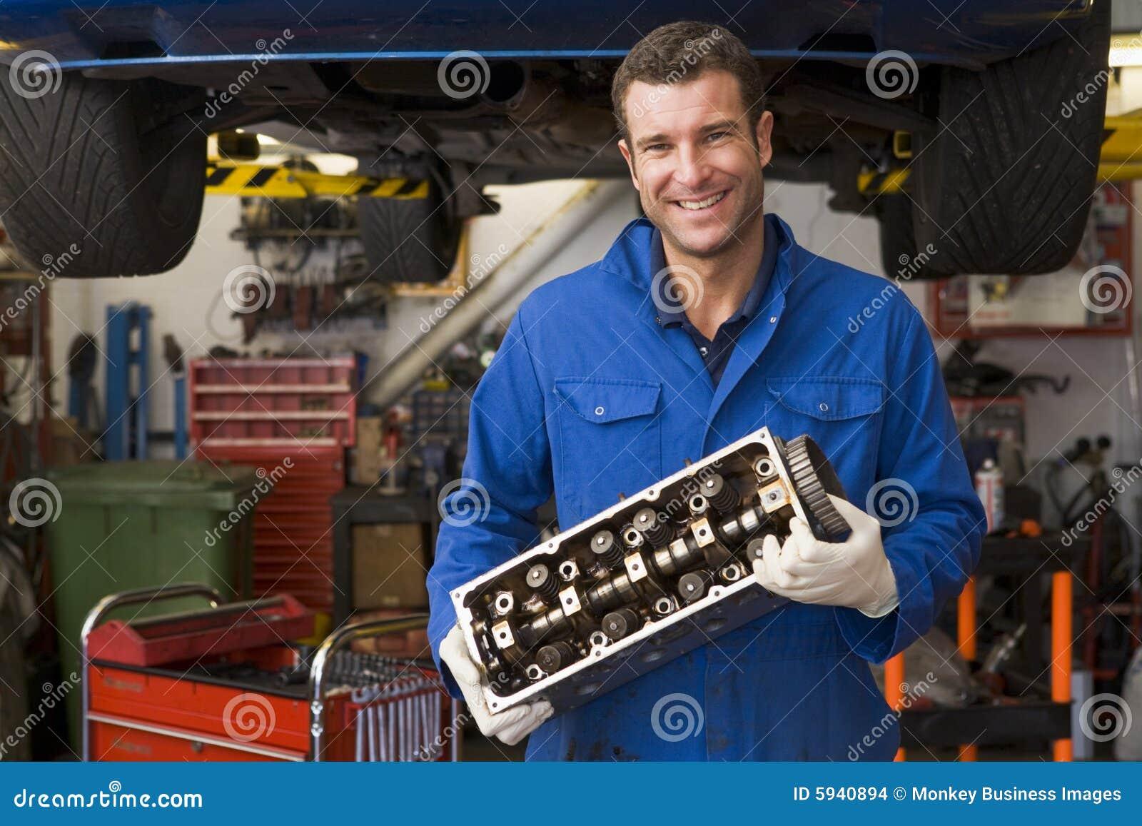 Sorriso da peça do carro da terra arrendada do mecânico