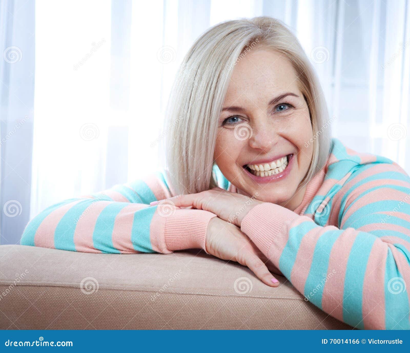 Sorriso de meia idade bonito ativo da mulher amigável e vista na câmera fim da face da mulher acima