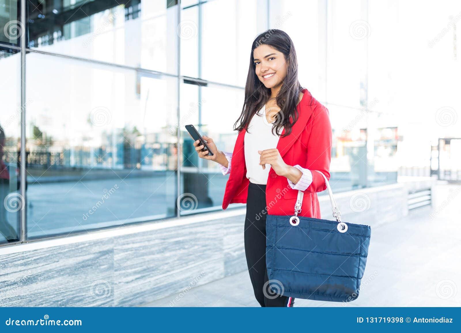 Sorriso executivo fêmea ao andar fora do escritório