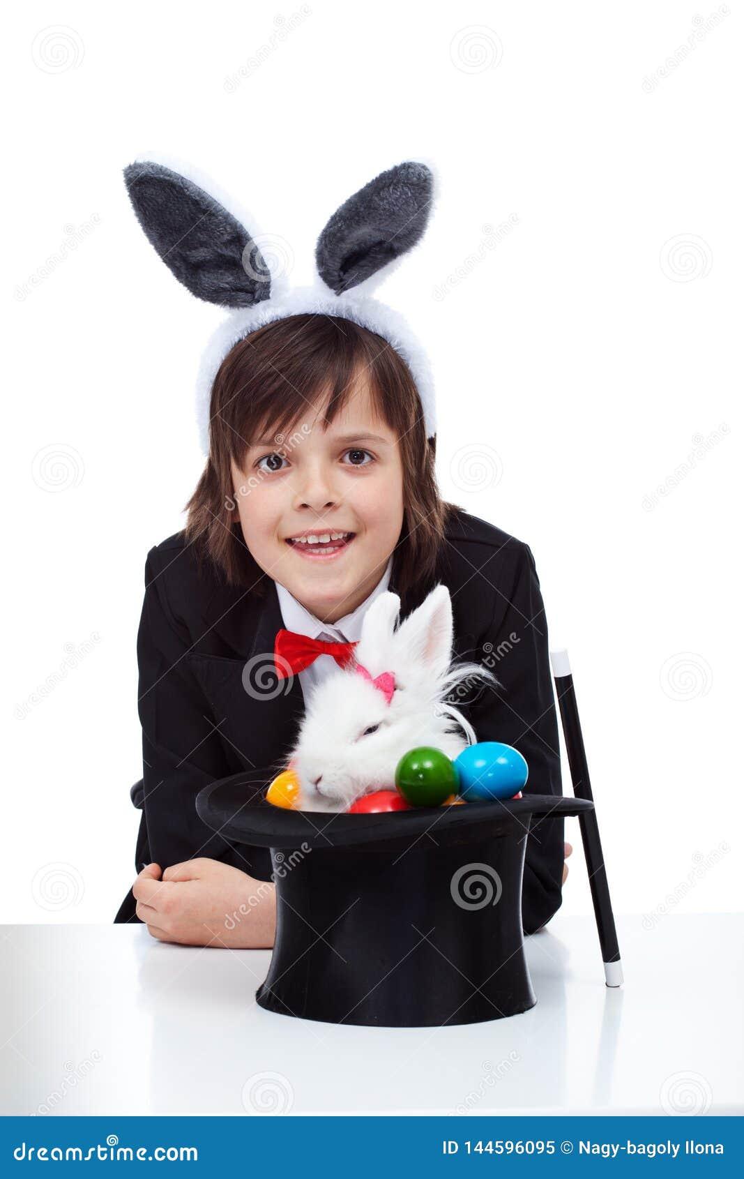 Sorriso feliz do menino do mágico após com sucesso ter puxado um coelhinho da Páscoa mal-humorado do chapéu