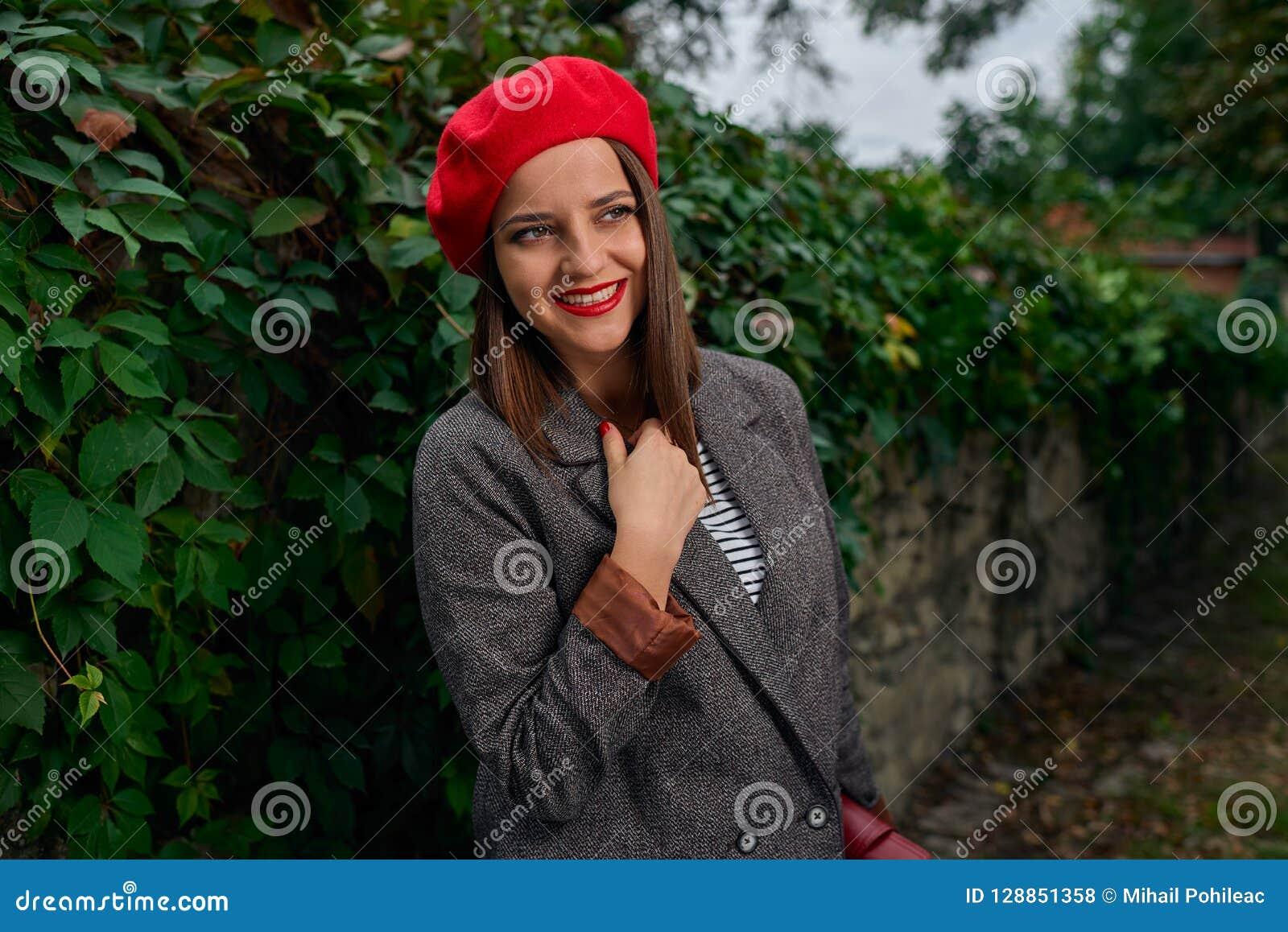 e1a5045b25c87 Retrato de uma jovem mulher entusiasmado com sorriso grande na boina  vermelha que olha longe da câmera perto de uma cerca de pedra coberta com a  vegetação