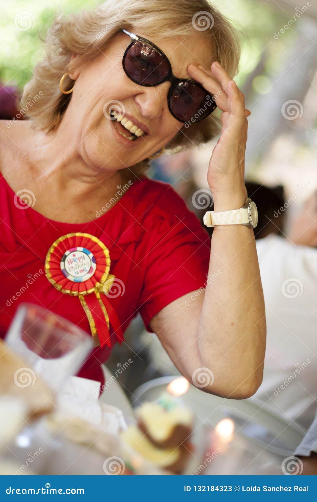 Sorriso louro da mulher mais idosa, vestindo uma camisa vermelha