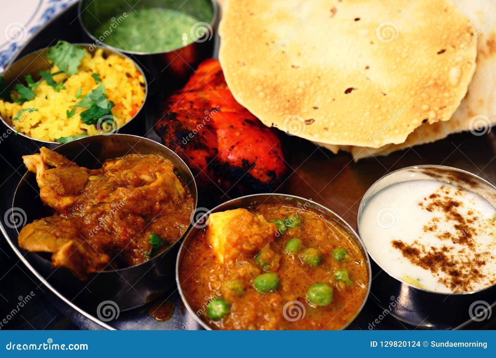 Sorterad indisk matuppsättning i magasinet, tandurihöna, naan bröd, yoghurt, traditionell curry, roti