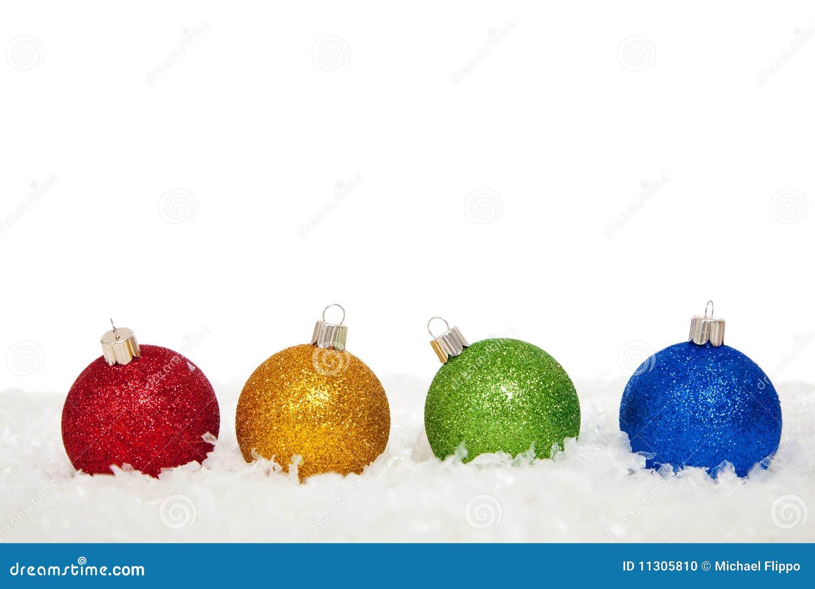 Sortierte farbige Weihnachtsverzierungen im Schnee