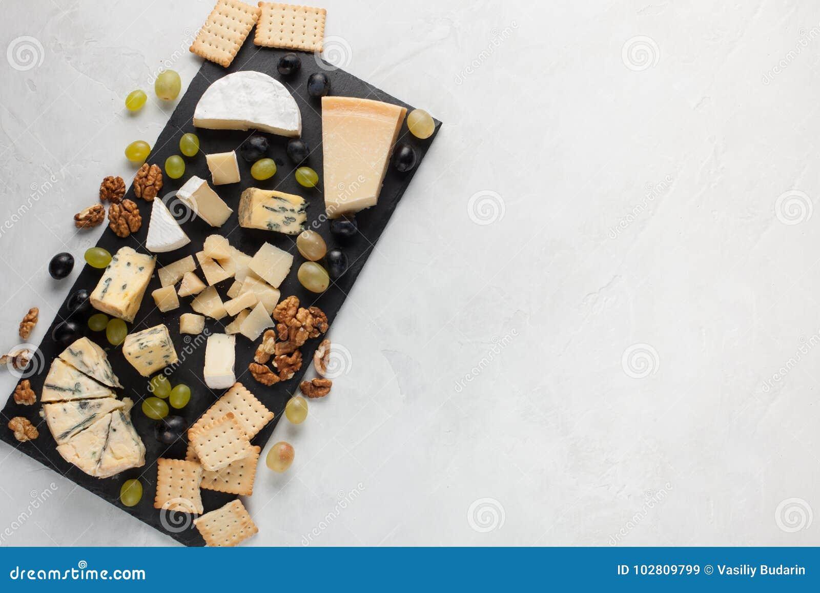 Sortierte Käse mit weißen Trauben, Walnüsse, Cracker und auf einem Steinbrett Lebensmittel für ein romantisches Datum an einem he