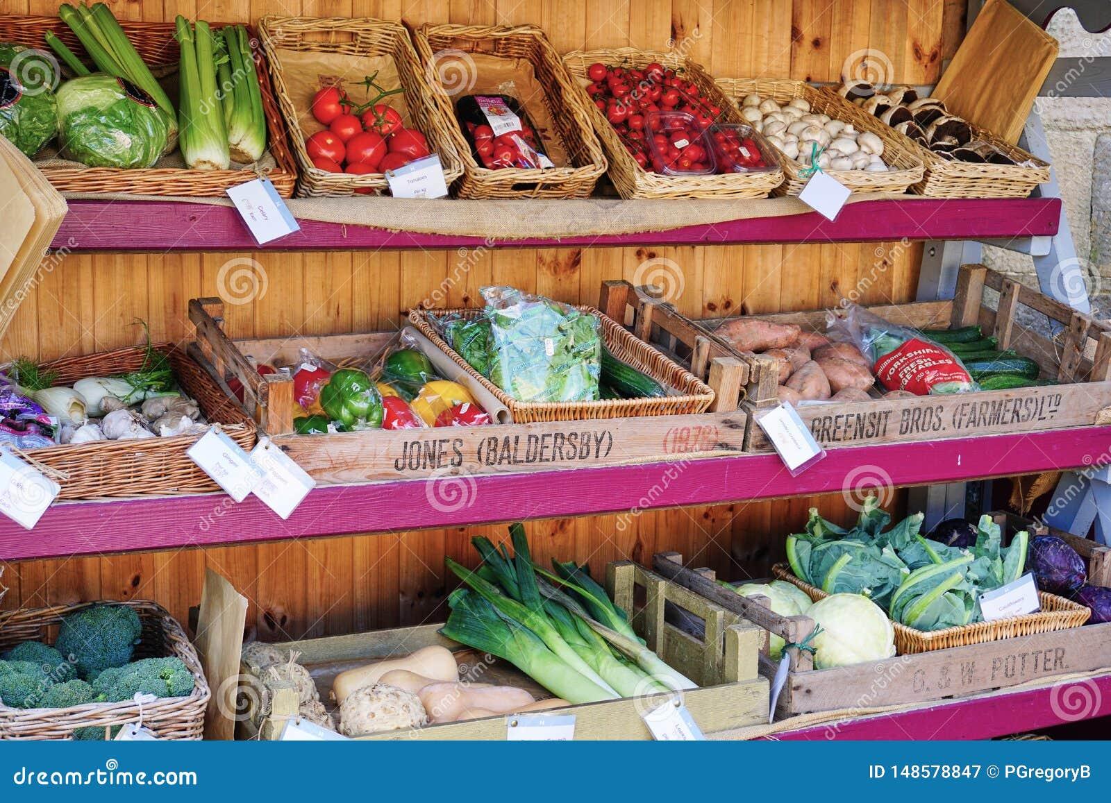 Sortiment av grönsaker på skärm på stånd i England, U K