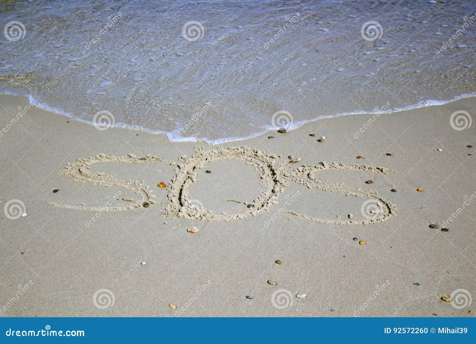 SOS - parola attinta la spiaggia di sabbia con l onda molle