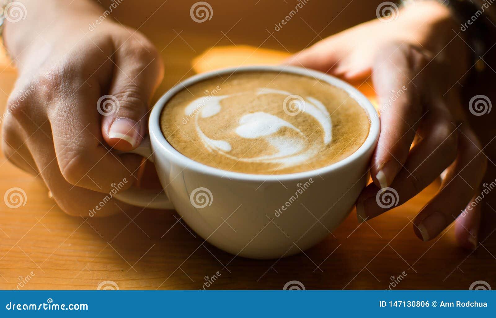 Sostener una taza de caf? con dos manos