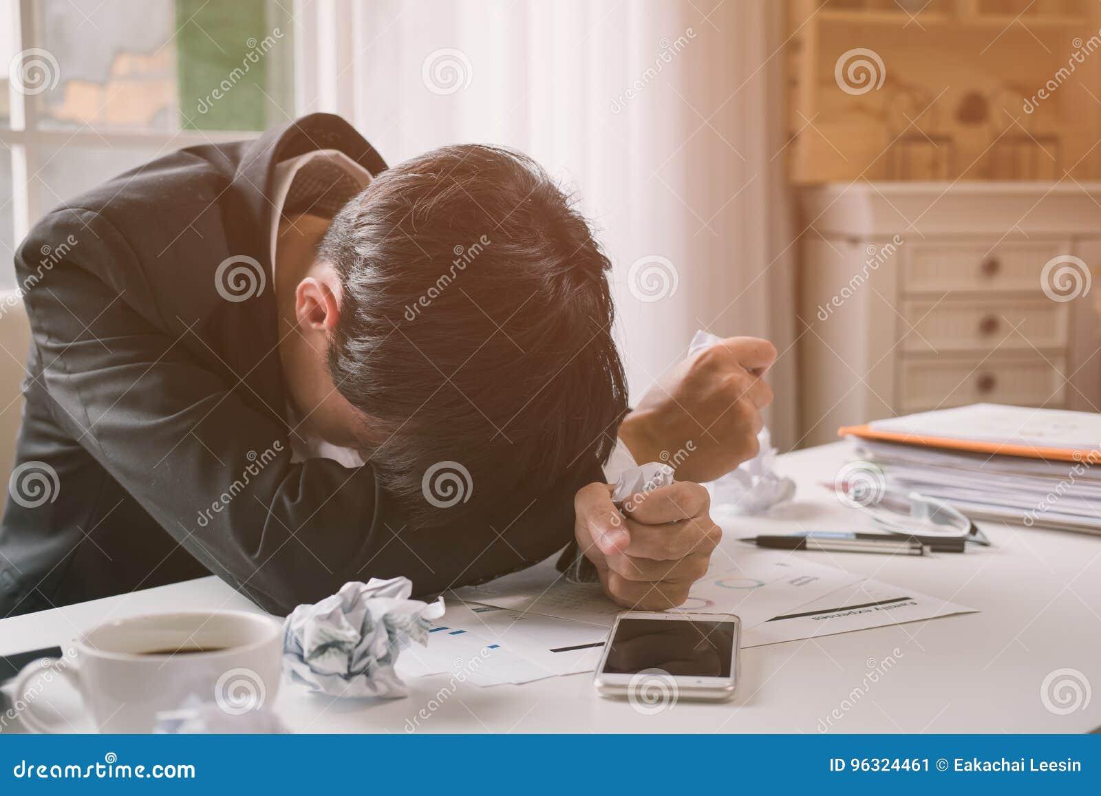 Soumis à une contrainte un homme d affaires tient sa tête de désespoir