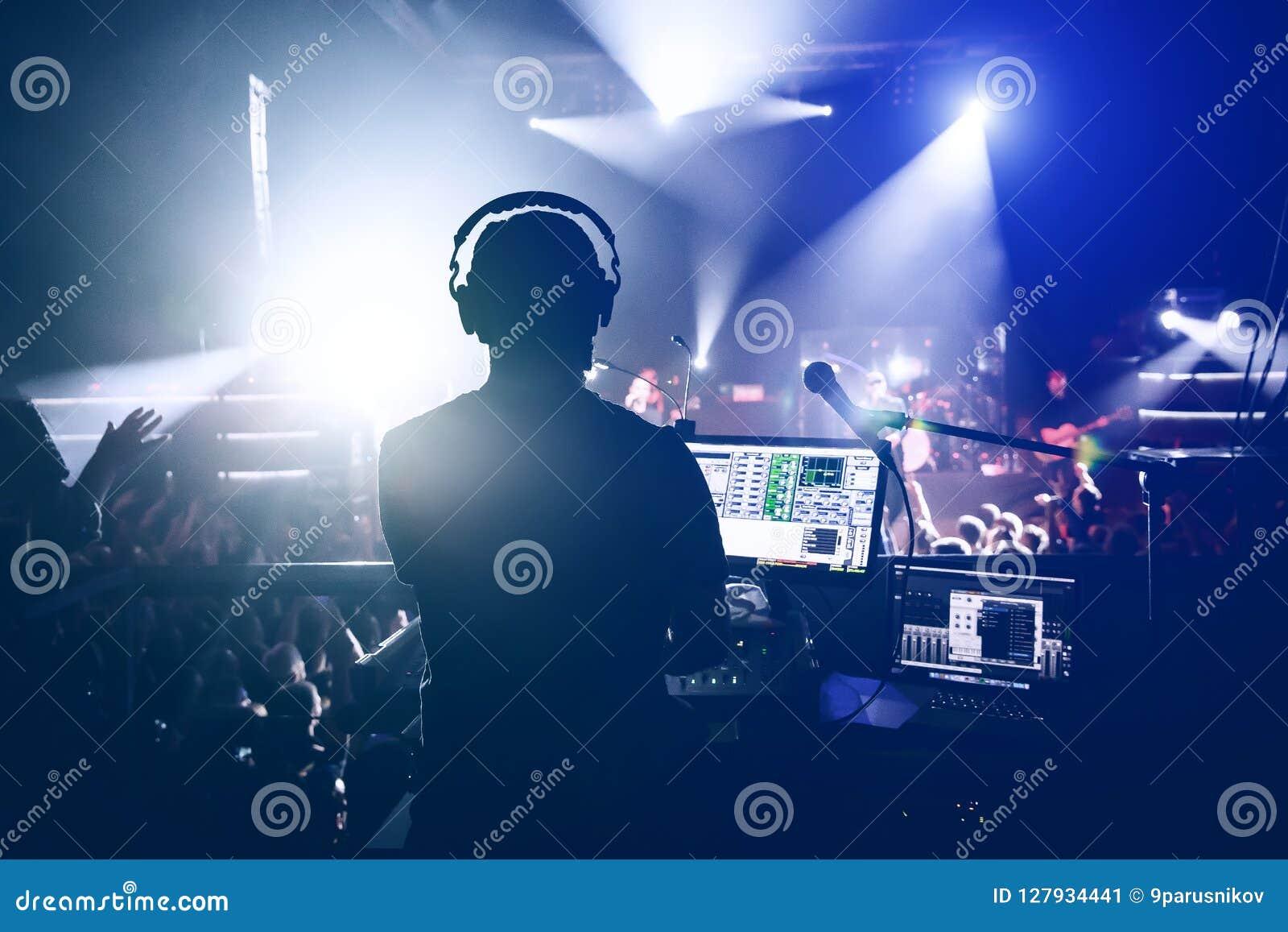 Sound engineer music producer adjusting and balancing audio on rock concert