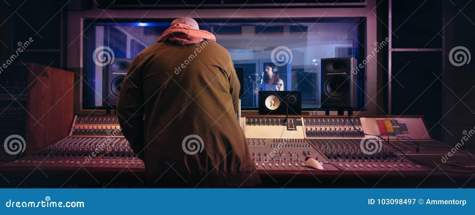 Musicians producing music in professional recording studio