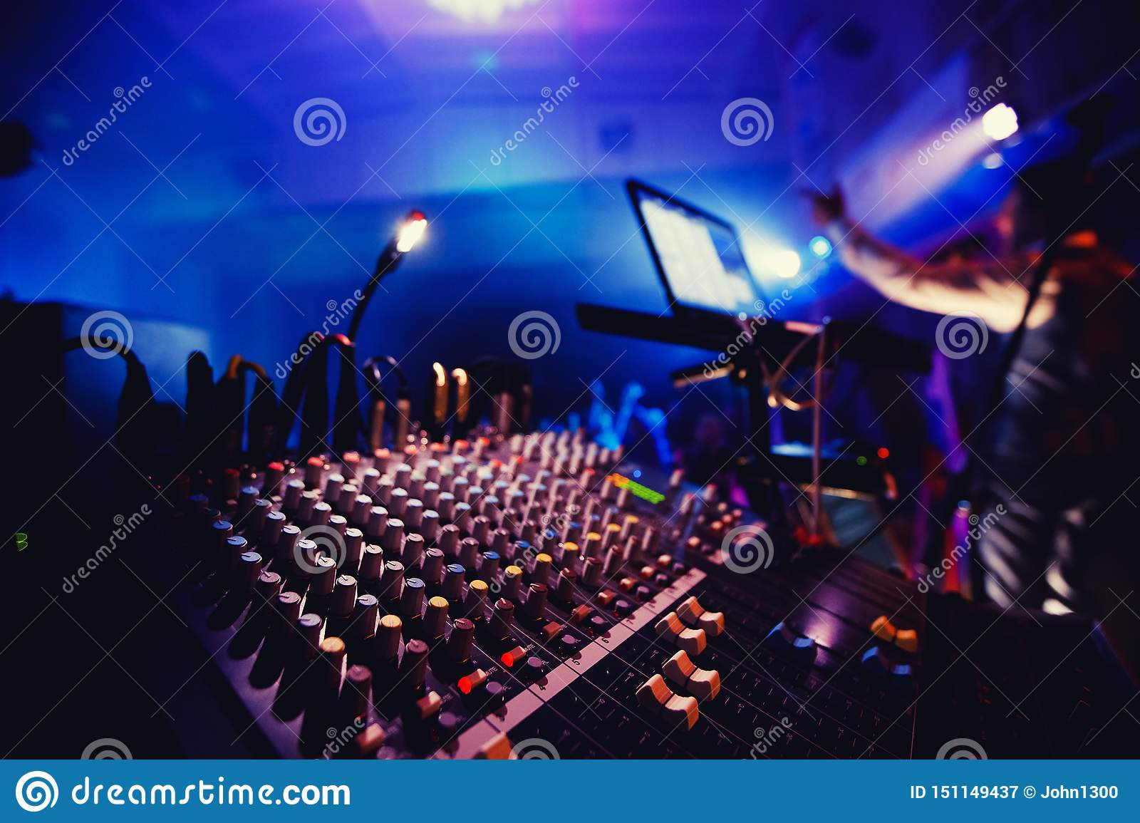 Sound equipment in nightclub party. DJ console, people dancing in background, around bright lights