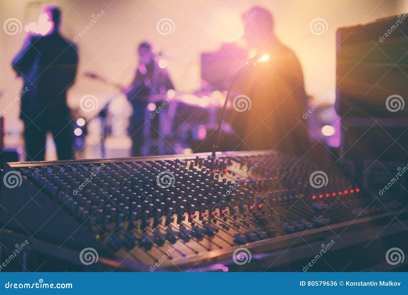 Soundman que trabaja en la consola de mezcla en sala de conciertos
