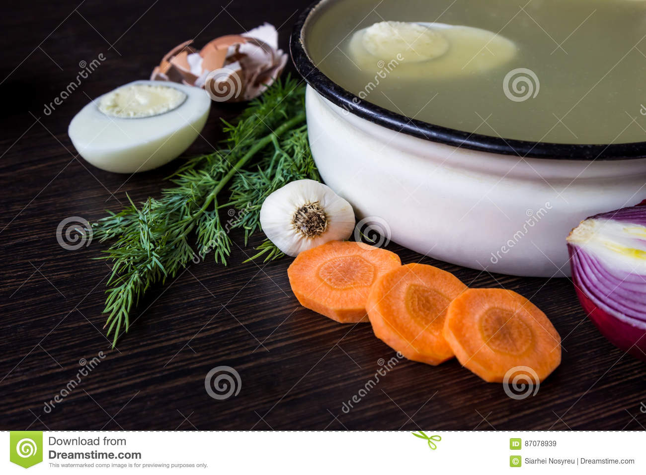 Soup with sorrel, vegetables and boiled egg, red onion, carrots, garlic, dill on dark wooden table.