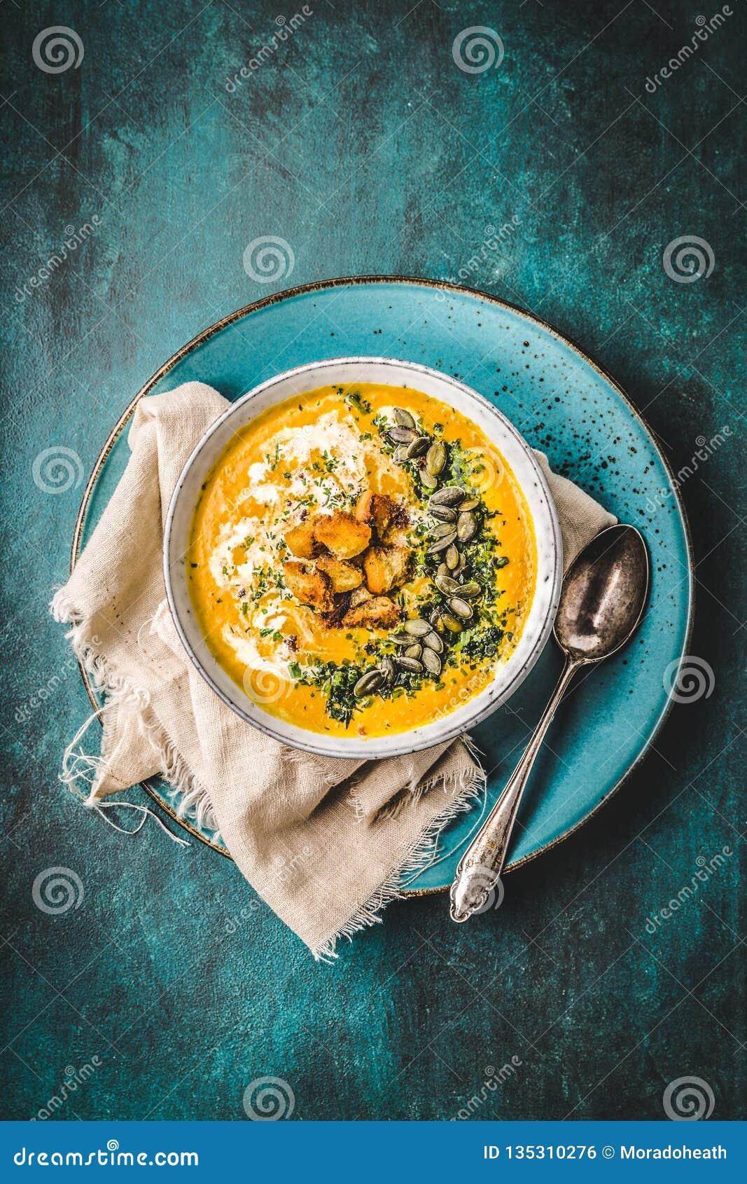 Soupe à potiron avec de la crème, des herbes et des graines