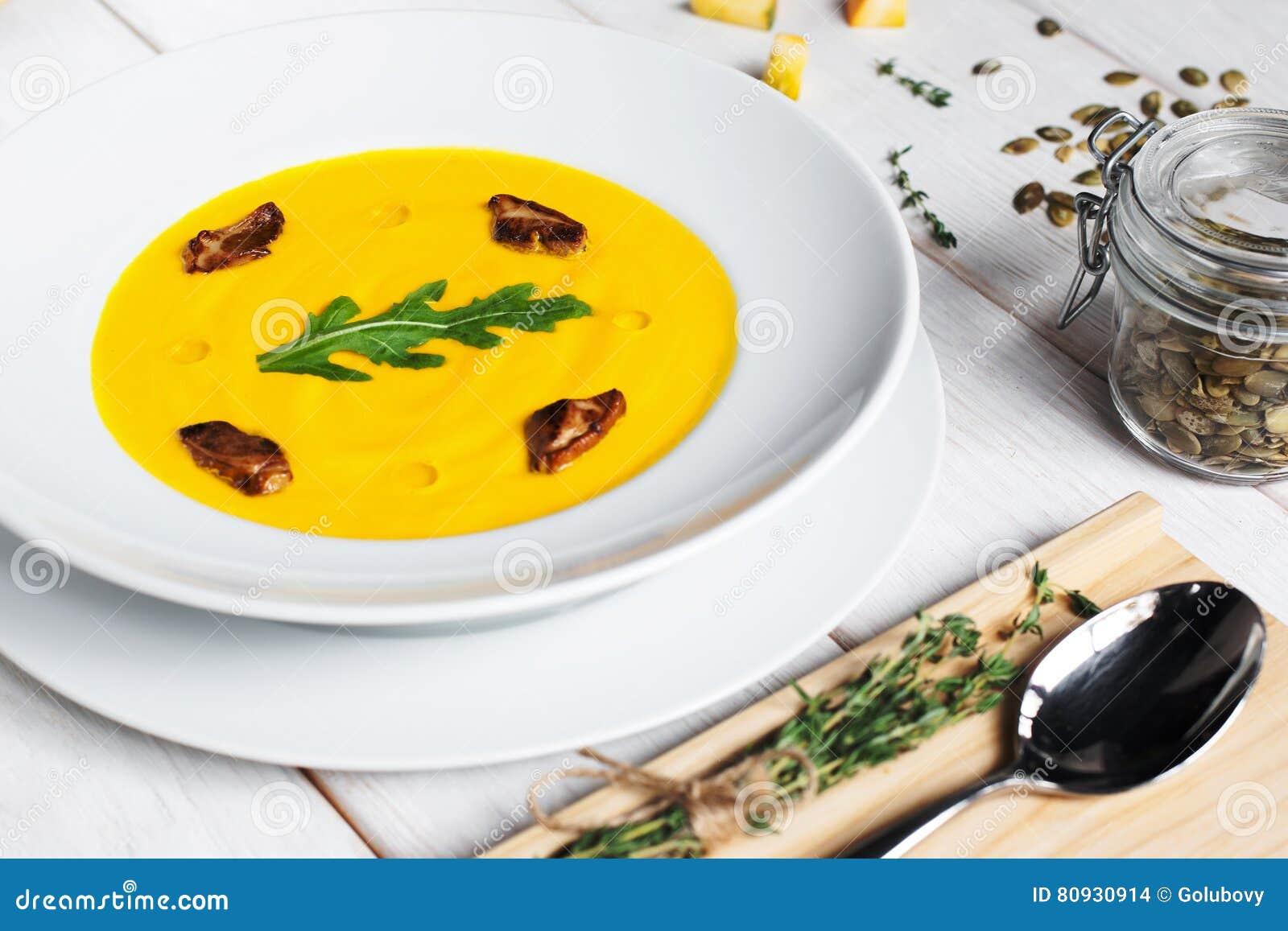 Soupe à potiron avec les graines et la cuillère sur la table