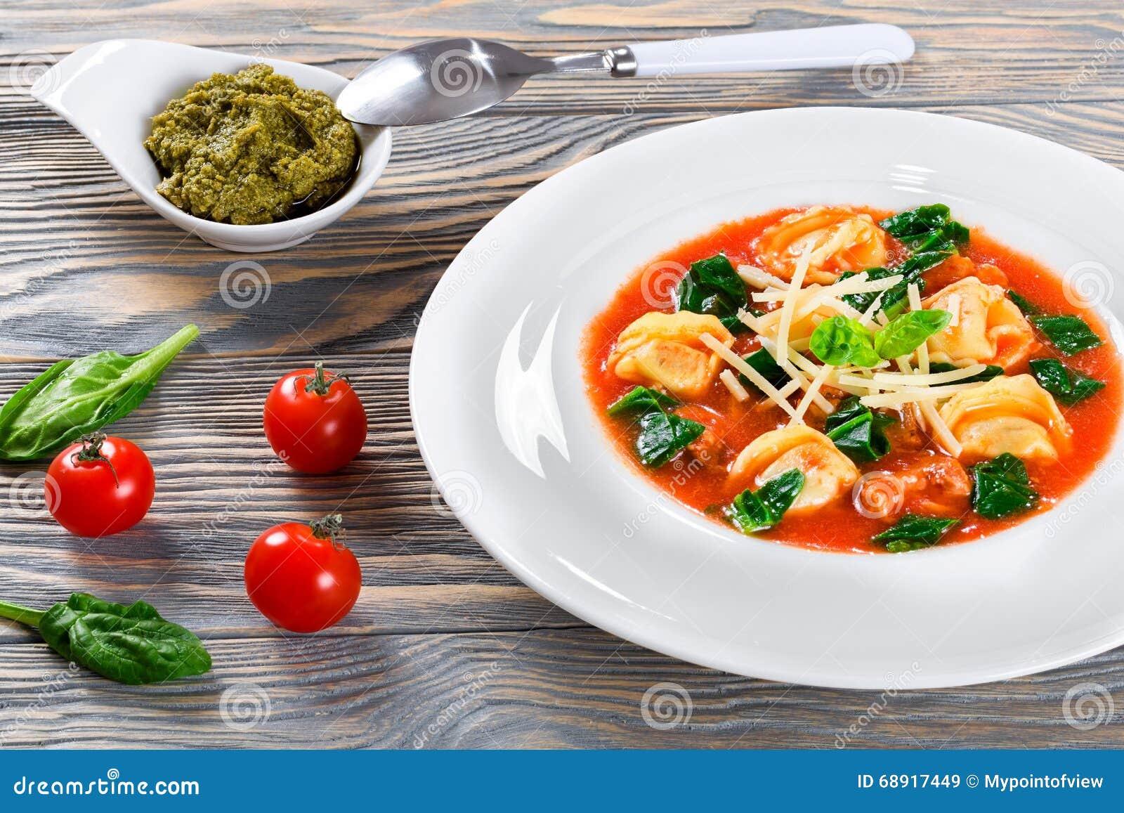 Soupe à Tortellini avec les saucisses italiennes, épinards, tomate, parmesan, pesto-sauce