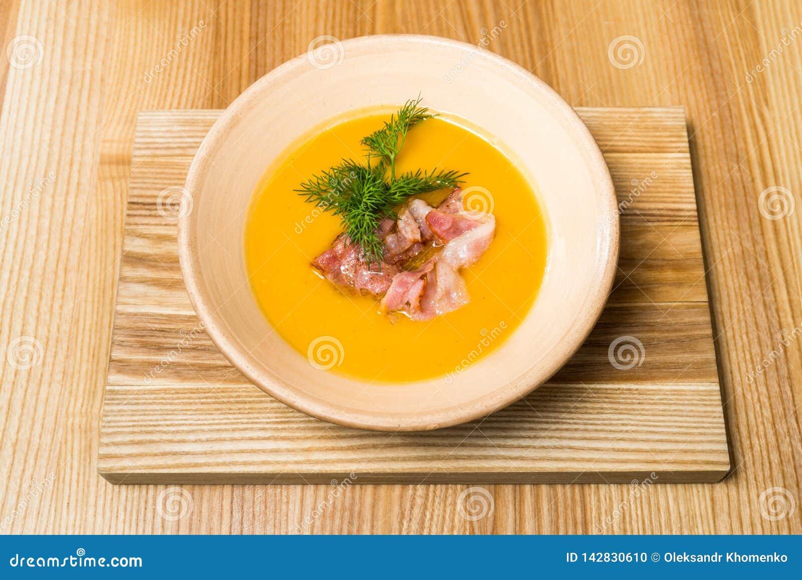 Soupe aux pois avec le lard sur une table en bois