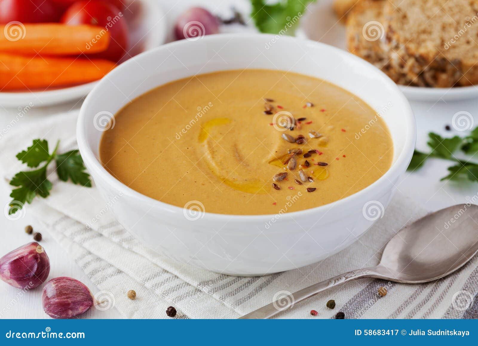 Soupe crème végétale végétarienne avec l aubergine et les carottes dans la cuvette blanche sur la table en bois