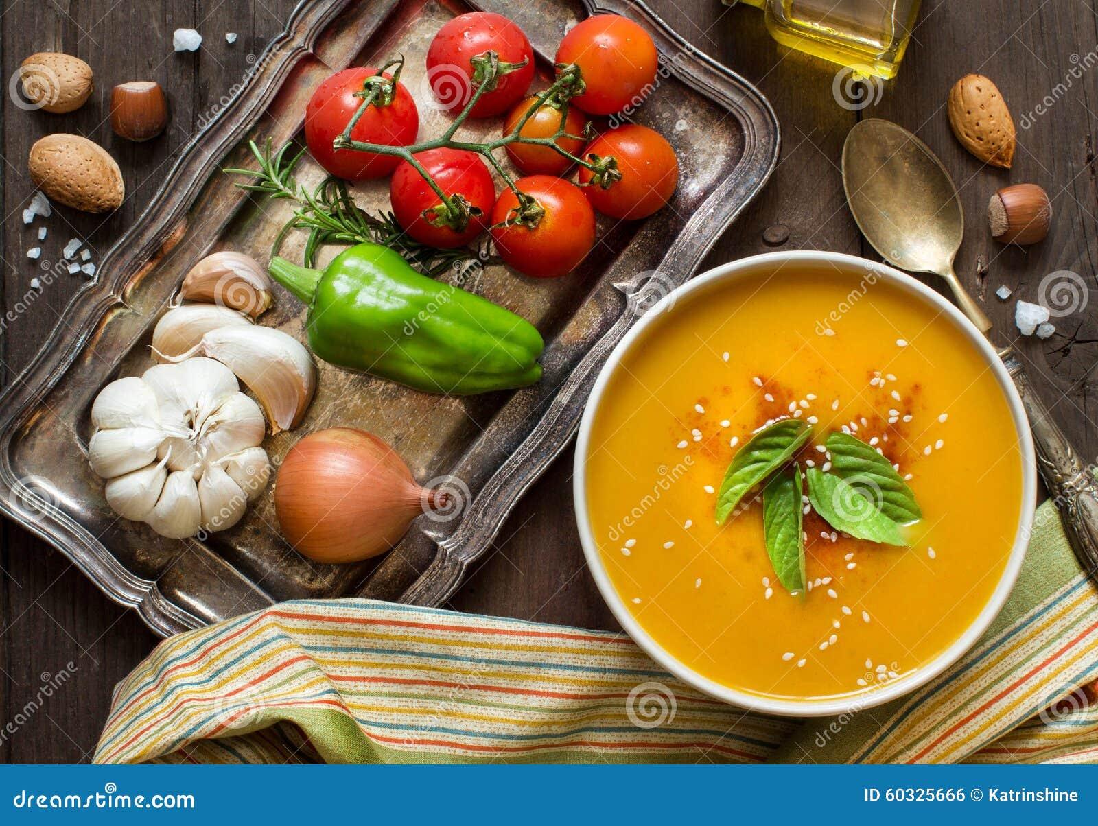 Soupe et légumes frais à potiron sur une table en bois