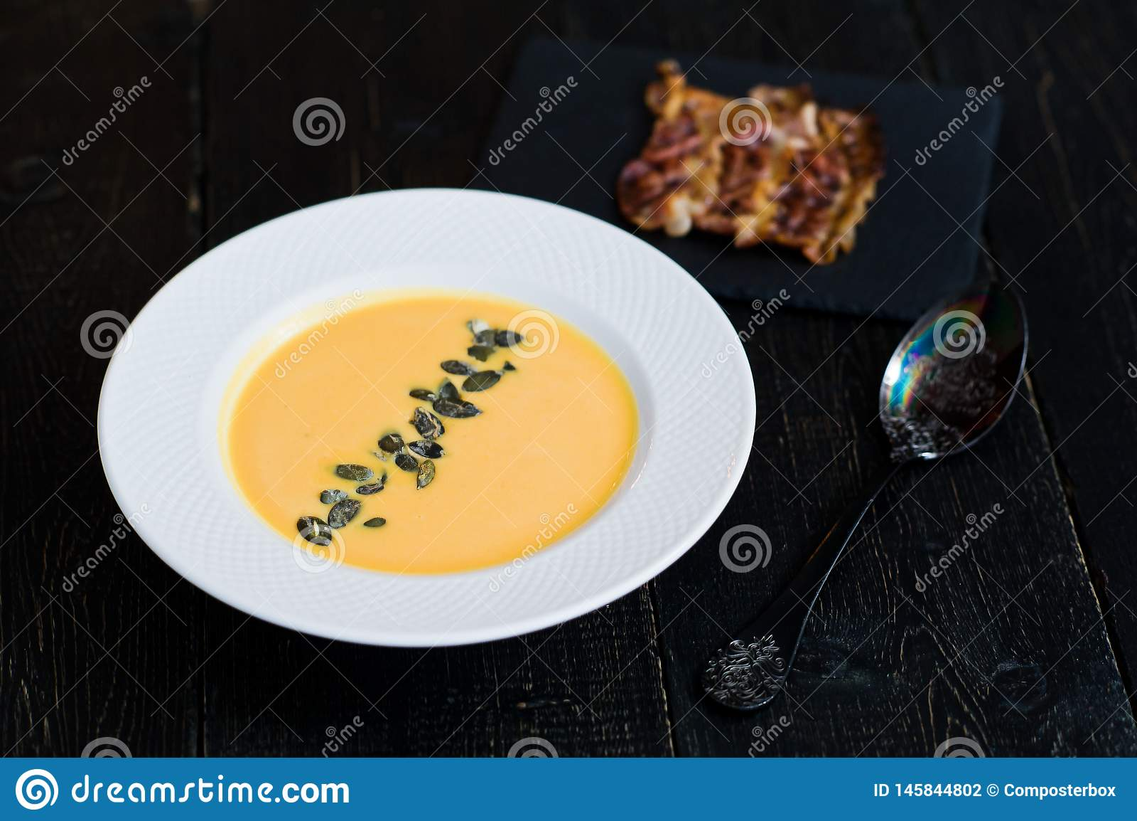 Soupe ? potiron avec le lard frit dans le plat blanc sur le fond noir
