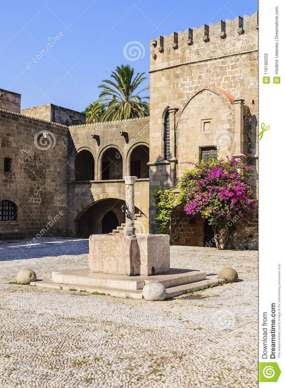 Source of water on the background of the knights Hospitallers in the square Argirokastro. Rhodes Old Town, Greece