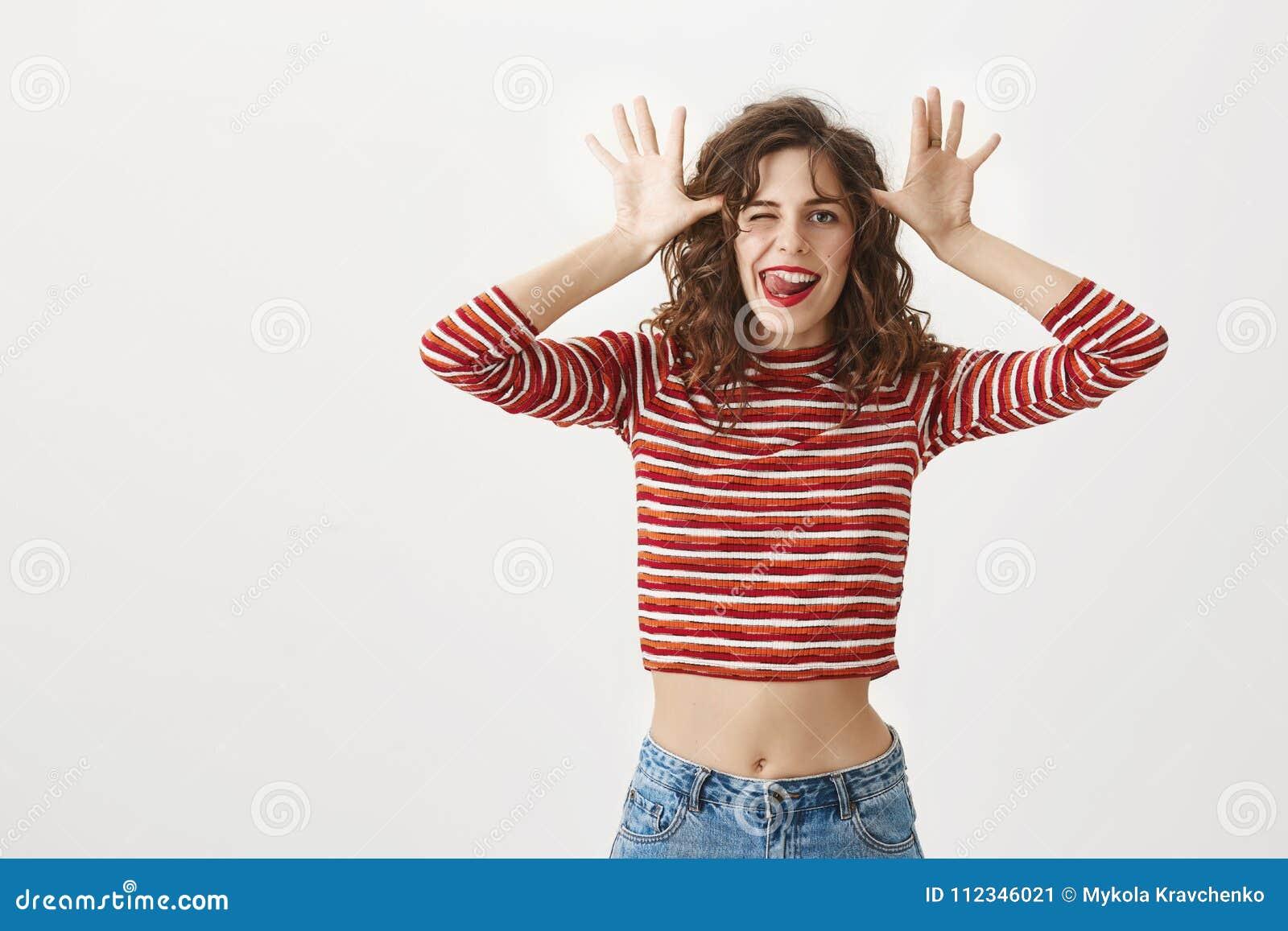 Sourire à l appareil-photo Femelle belle positive joyeuse dans l équipement élégant, faisant des visages, clignant de l oeil et m