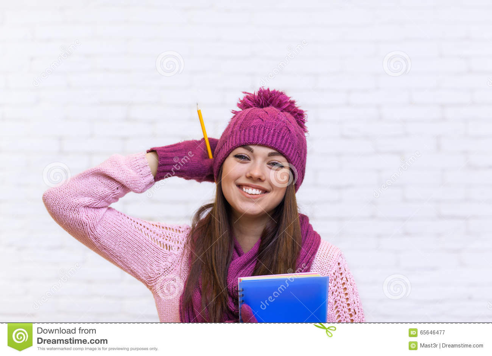 Sourire attrayant de Girl Happy Emotional d étudiant dans le chapeau rose tenant le crayon de dossier