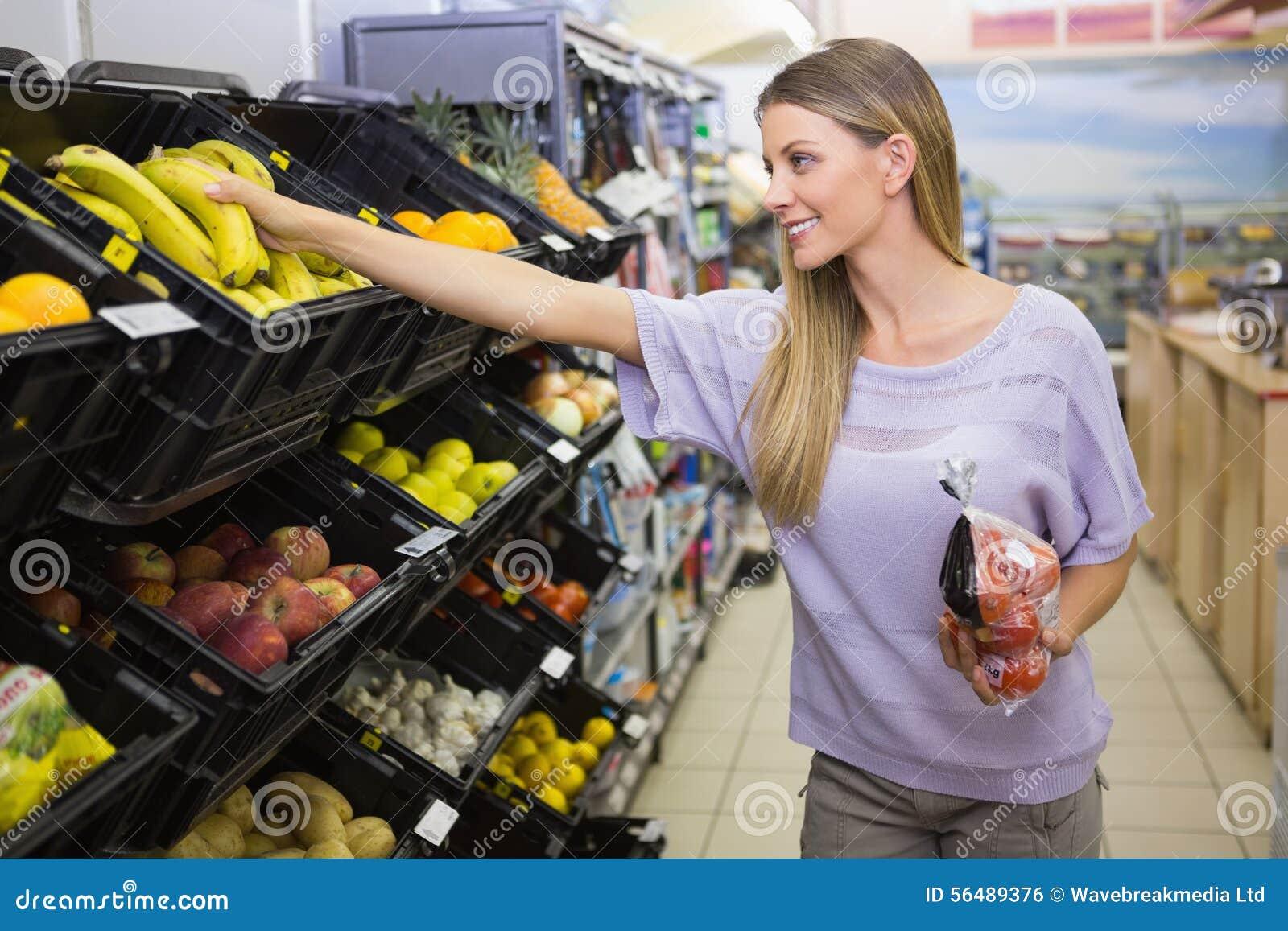 Sourire bananes de achat de femme assez blonde