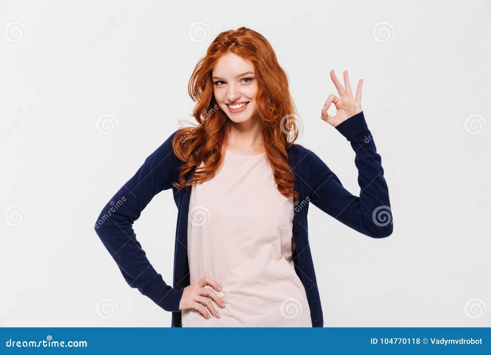 Sourire dame rousse assez jeune montrant le geste correct